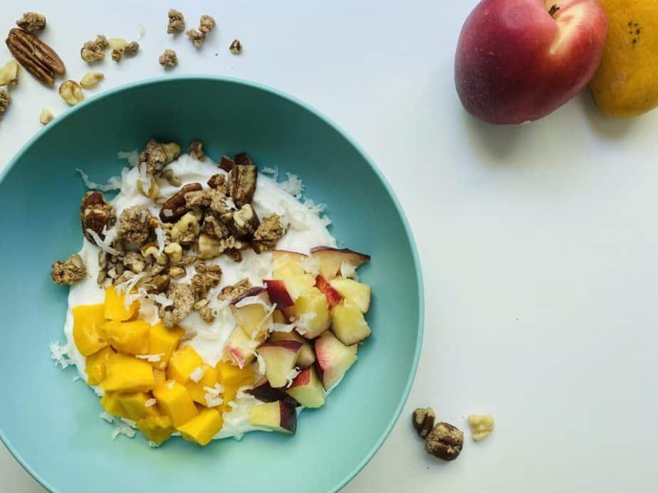 fruit and yogurt parfait in a turqoiuse bowl on a white table