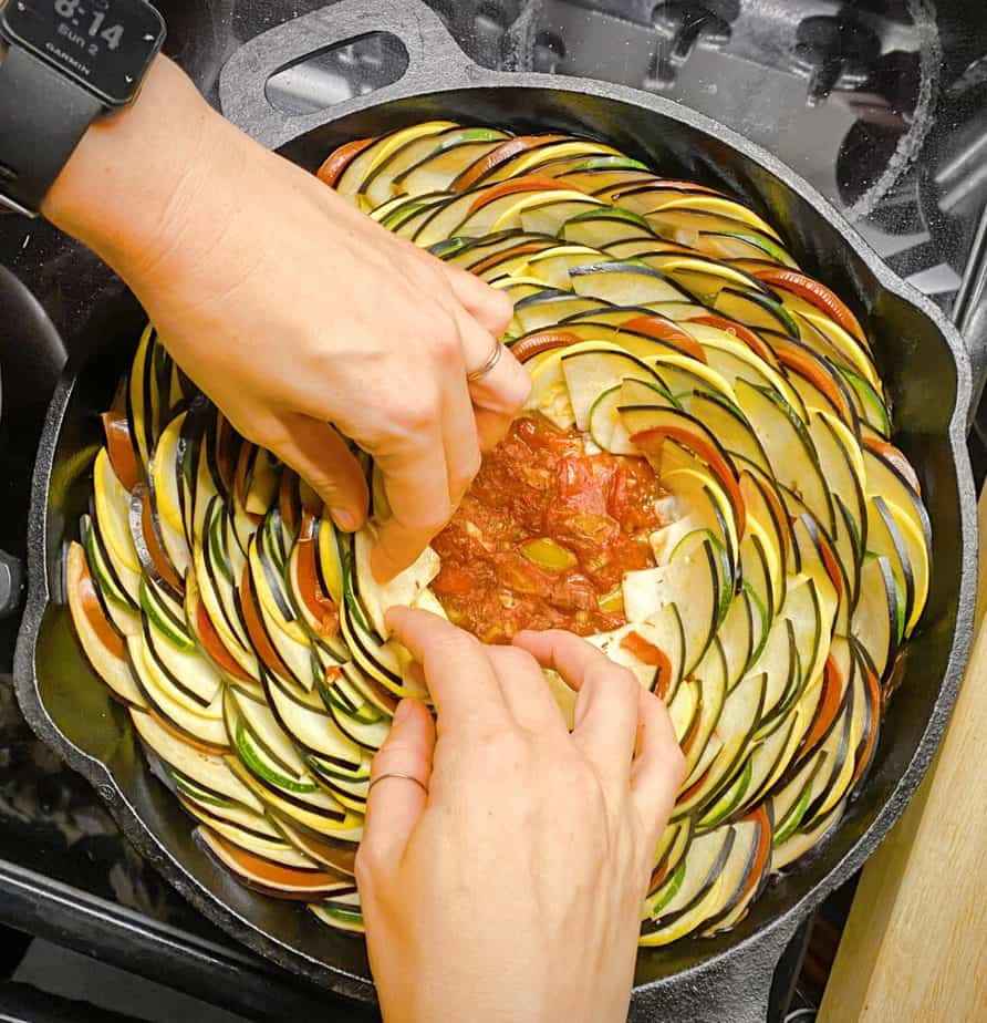 Overhead shot of me assembling the vegetables for the ratatouille in a cast iron skillet. You can still see the tomato-bell pepper sauce in the middle of the pan where I haven't finished arranging vegetables.