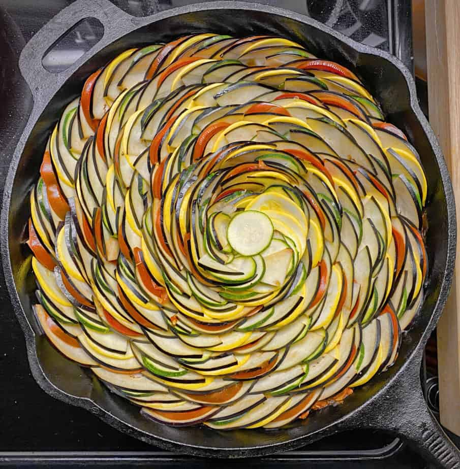 Completed spiral of ratatouille veggies in a cast iron skillet