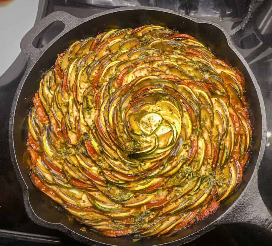 Completed, baked ratatouille in cast iron. You can see the lovely spiral pattern and places on the veggies where it's become slightly charred. Beautiful!