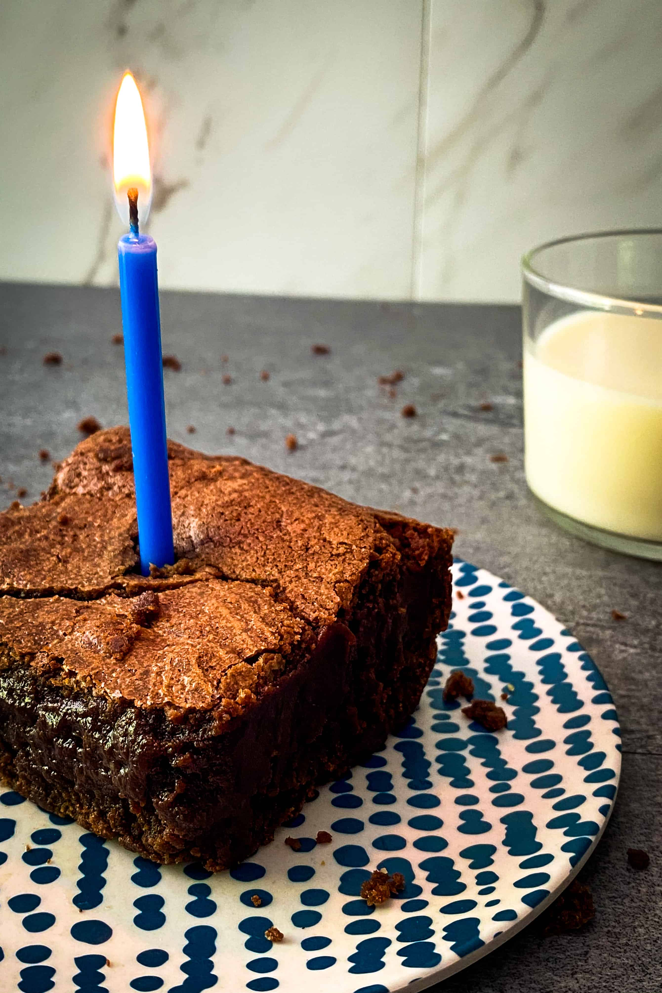Julia Child's favorite brownies with a candle to celebrate her 108th birthday and a glass of almond milk
