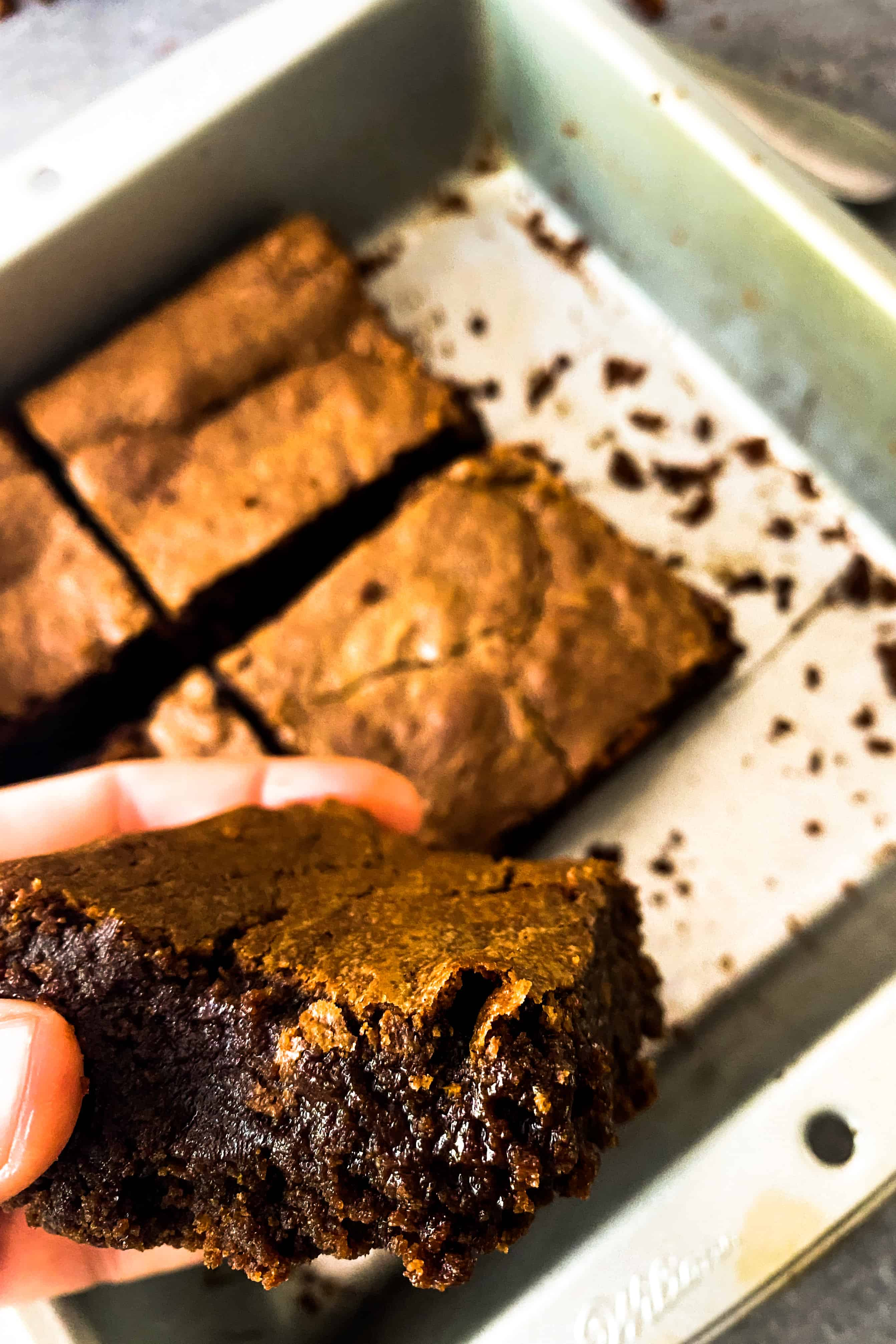 Close up shot of Julia Child's favorite brownies. One is in my hand and you can see the crazy rich detail of the brownie.