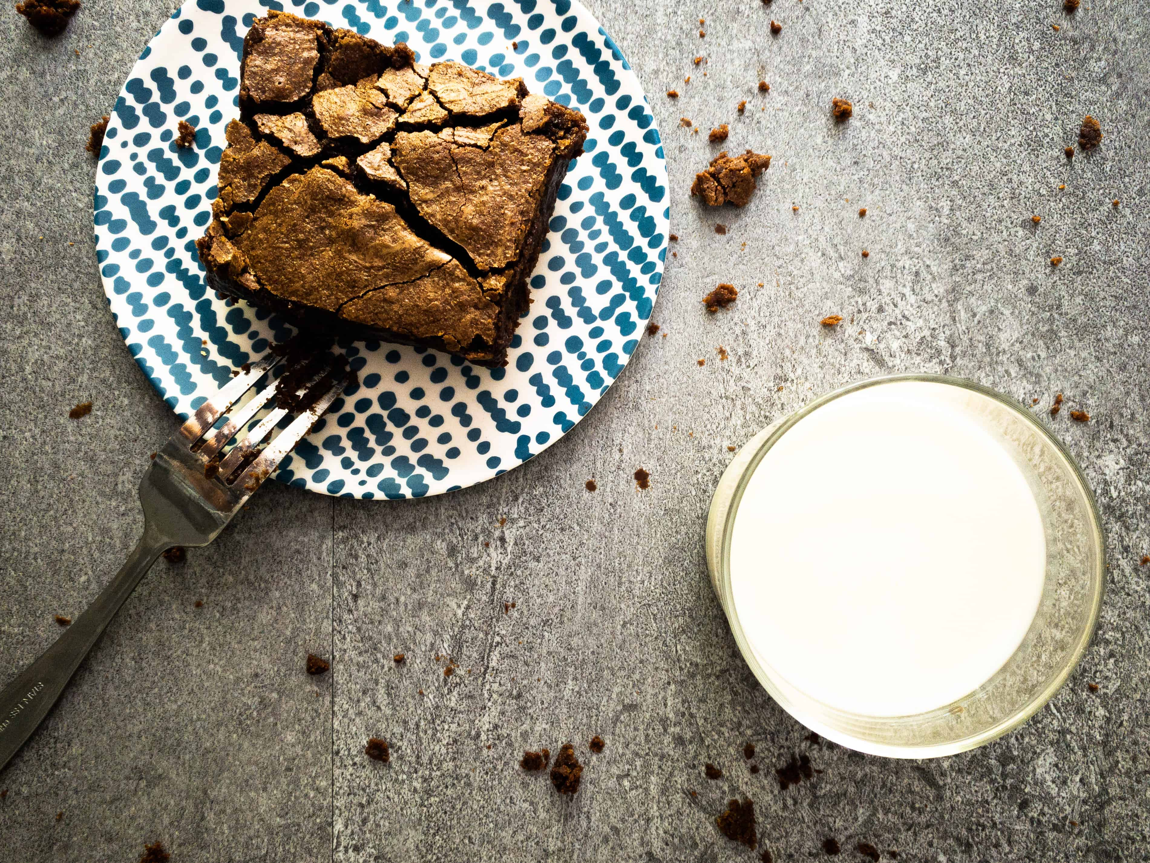 Overhead shot of brownie on a plate with a glass of milk. The fork is covered in fudgy particles sticking to it