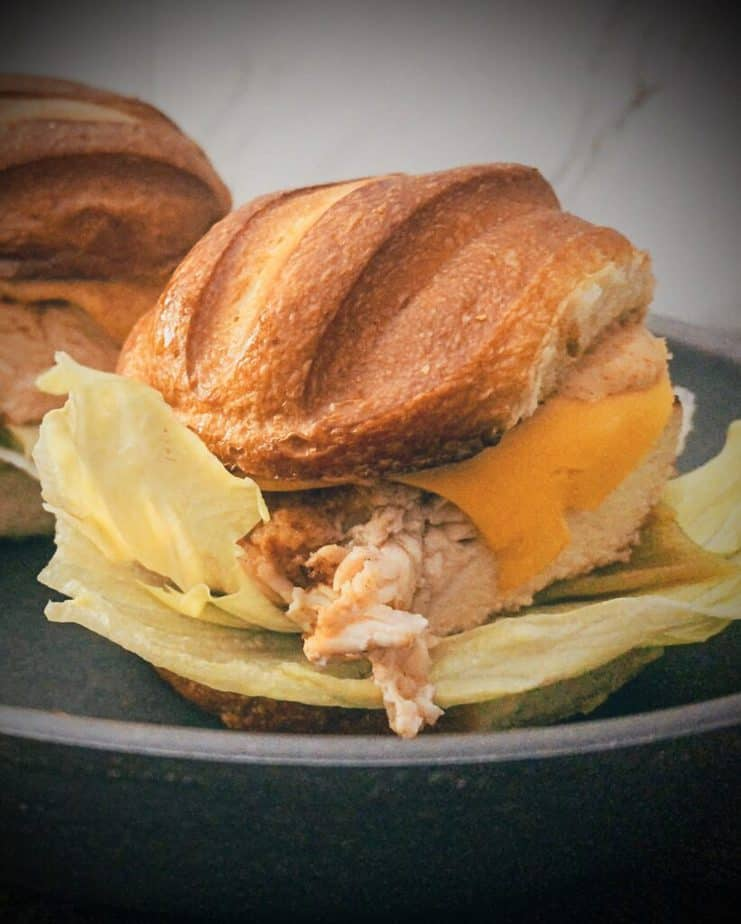 Golden French Bread style bun with melted american cheese, adobo mayonnaise, grilled chicken breast, green chili and iceberg lettuce