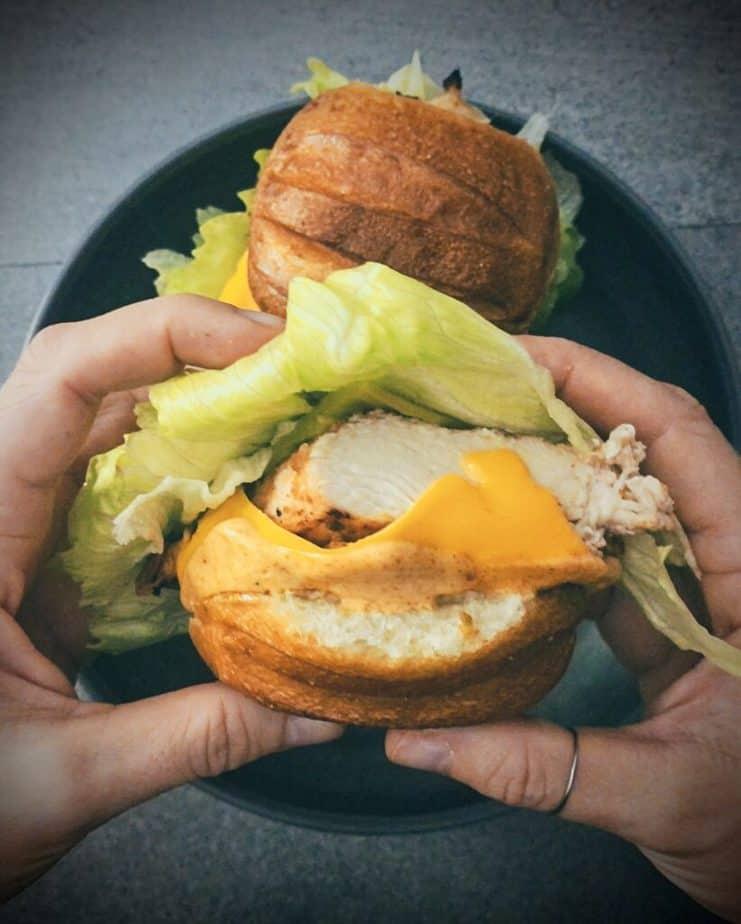 Two hands holding Santa Fe chicken sandwich