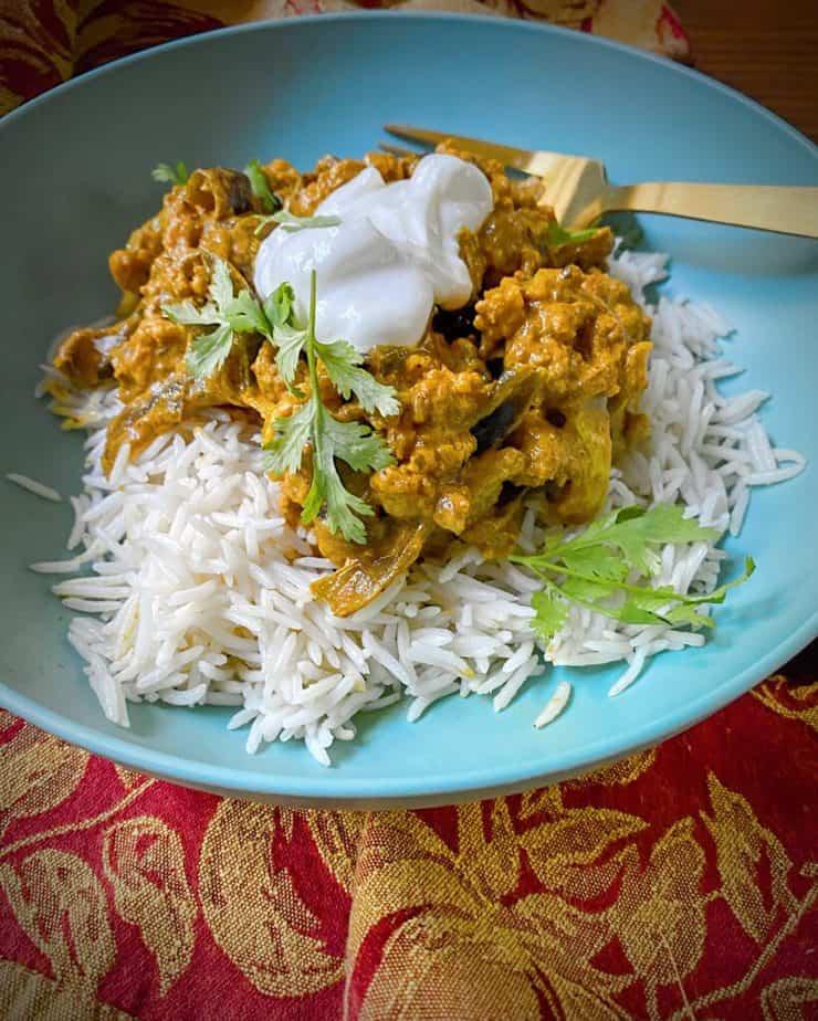 hero shot of vegan cauliflower tikka masala over basmati rice in a turquoise bowl on a fall themed dish towel