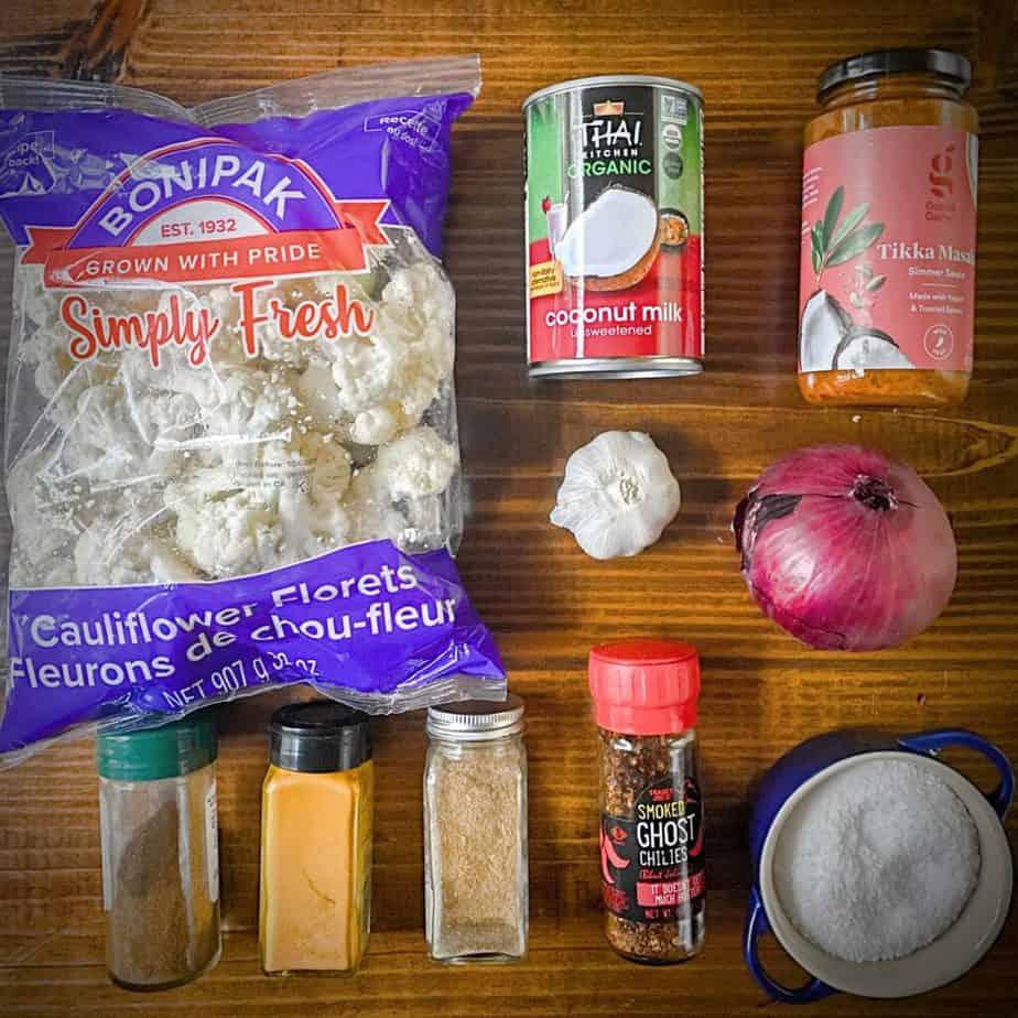 a bag of cauliflower florets, a can of coconut milk, a jar of tikka masala simmer sauce, a red onion, blue salt cellar and 4 spice jars