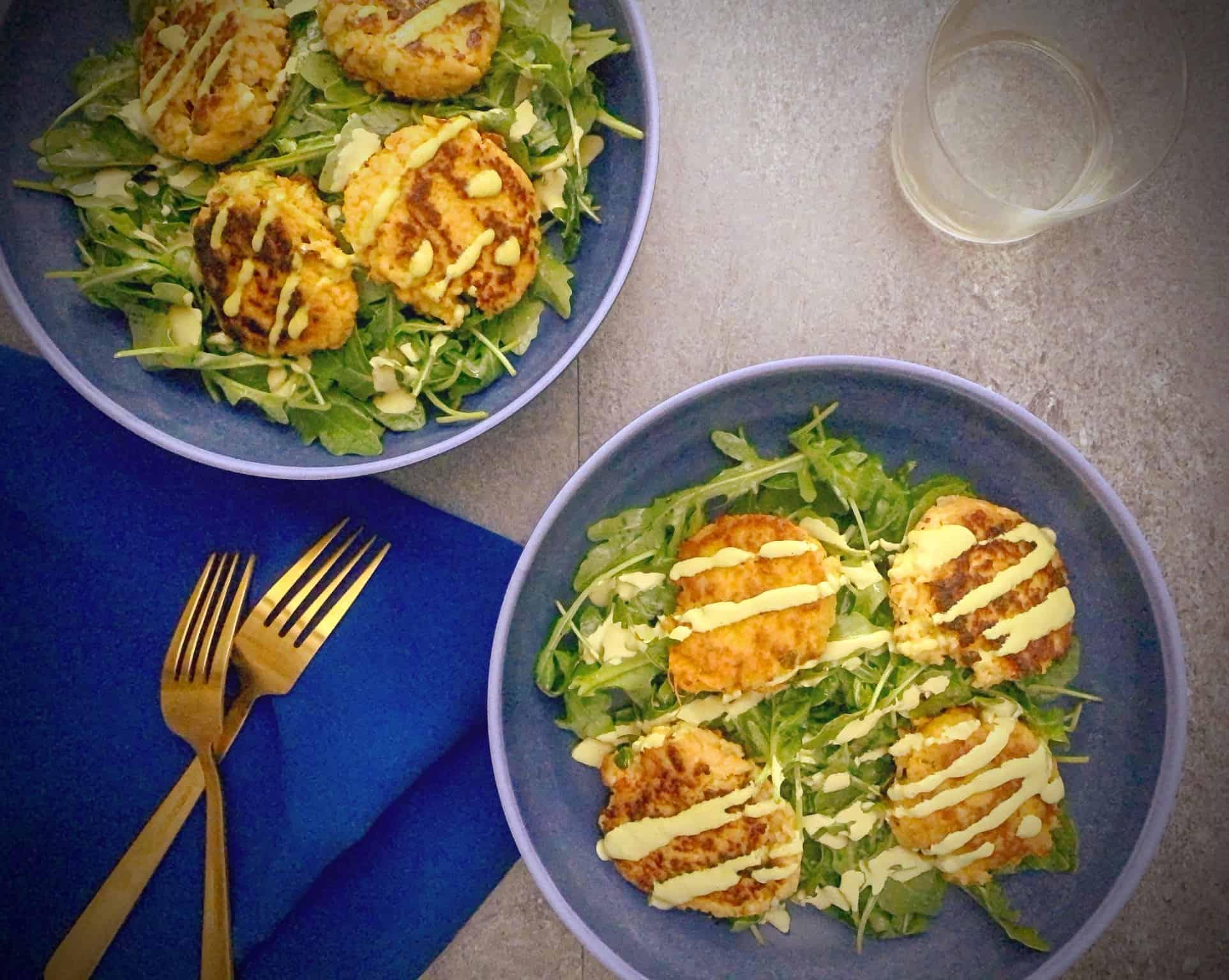 two pasta bowls with sweet potato salmon cakes over arugula