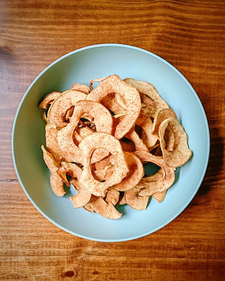 finished homemade apple chips in a turquoise bowl on a dark wooden background