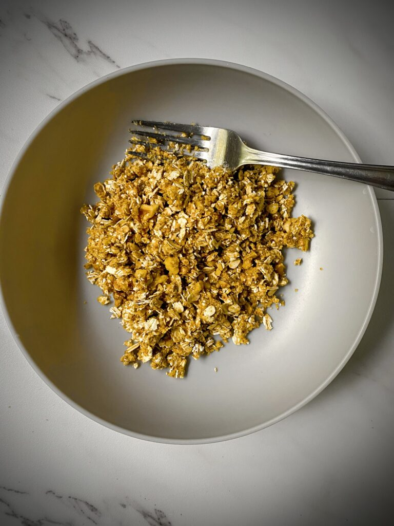 healthy apple crisp topping in a grey pasta bowl with a silver fork on a white marble background