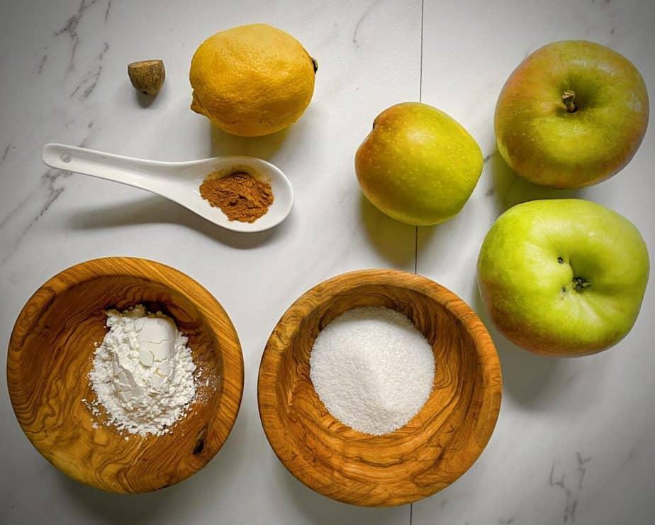 3 gravenstein apples, 1 lemon, a whole nutmeg, cinnamon, sugar and cornstarch as mis en place for apple filling