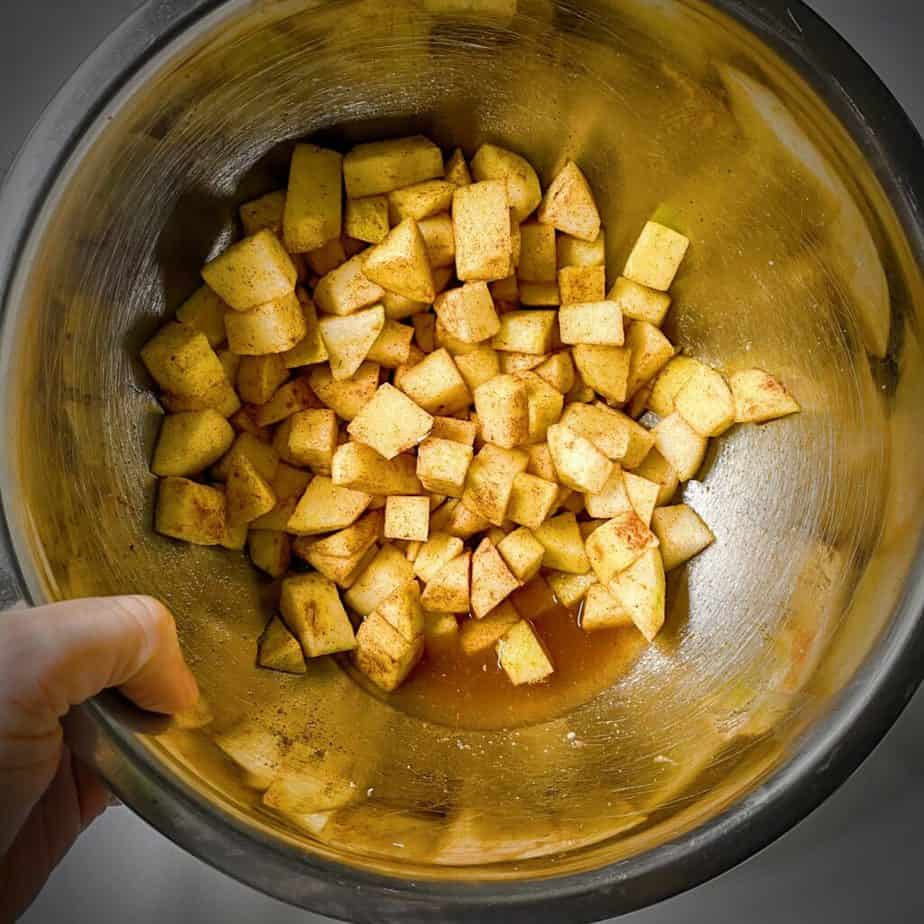 Apples that have been properly macerated in sugar in a metal bowl being tilted by a hand to show juices