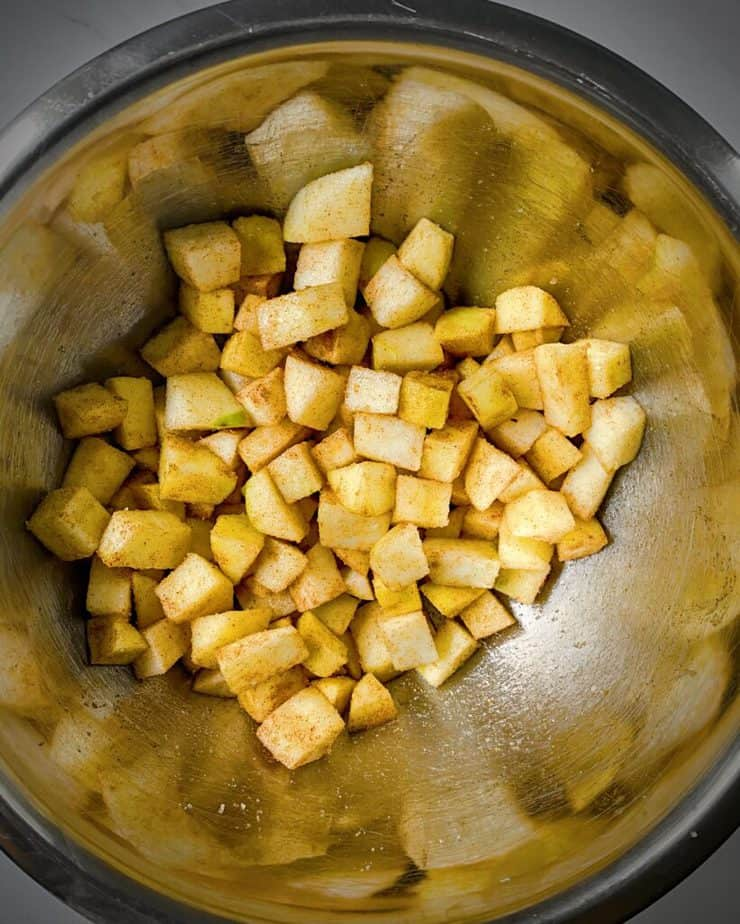 apples that have been peeled, diced and are tossed with spices and sugar