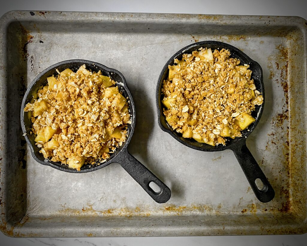 healthy apple crisp for two in two mini cast iron skillets on a sheet tray ready to bake