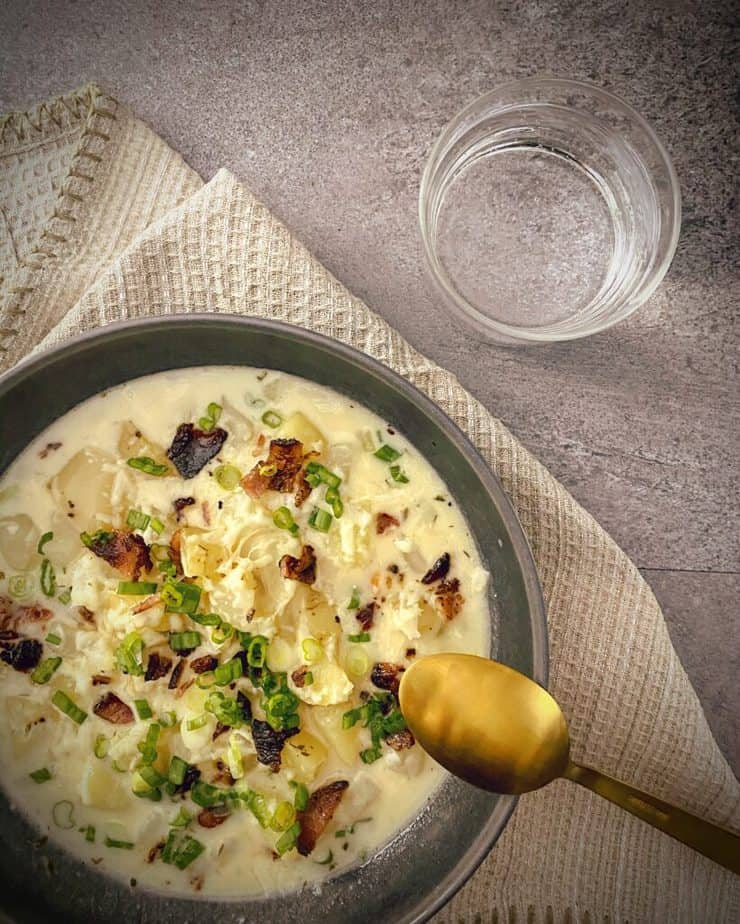 instant pot loaded baked potato soup in a dark grey pasta bowl topped with white cheddar, green onions and bacon pieces with a gold spoon, tan waffle knit napkin on a grey slate background with a glass of sparkling water