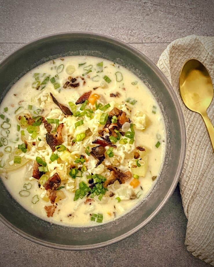 close up shot of instant pot loaded baked potato soup in a dark grey pasta bowl topped with white cheddar, green onions and bacon pieces with a gold spoon, tan waffle knit napkin on a grey slate background