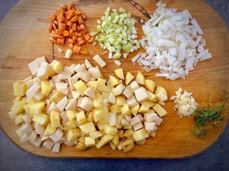 diced carrots, celery, onion, gold and russet potatoes, minced garlic and thyme on a wooden cutting board