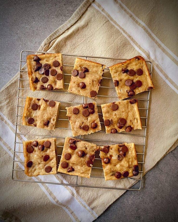 overhead shot of 9 healthy banana chocolate chip breakfast bars on a cooling rack on a tan tea towel