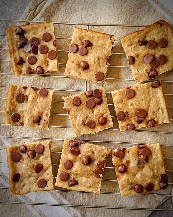 overhead shot of 9 squares of banana chocolate chip healthy breakfast bars on a cooling rack on a tan tea towel