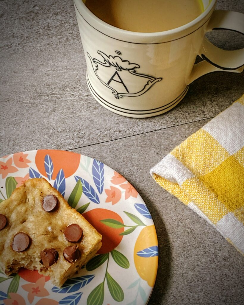 healthy breakfast bar on a floral plate with a yellow and white gingham towel and a mug of coffee with an A emblazoned on the front