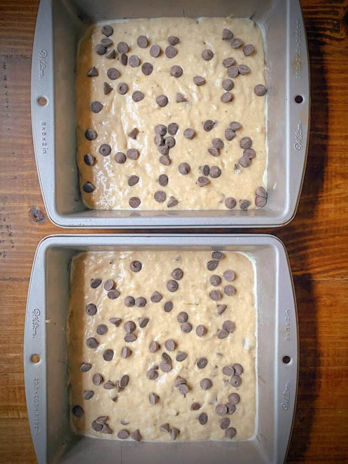 two 8 x 8 baking tins filled with healthy banana chocolate chip breakfast bar batter and sprinkled with chocolate chips on top on a wooden table