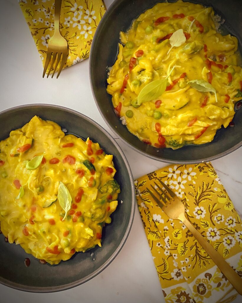 overhead shot of butternut apple soup turned into a quick weeknight curry with rotisserie chicken, green beans, peas, zucchini, broccoli in grey pasta bowls over cauliflower rice with yellow floral napkins and gold forks