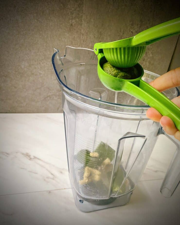 hand squeezing lime juice into blender pitcher with jalapeño and ginger