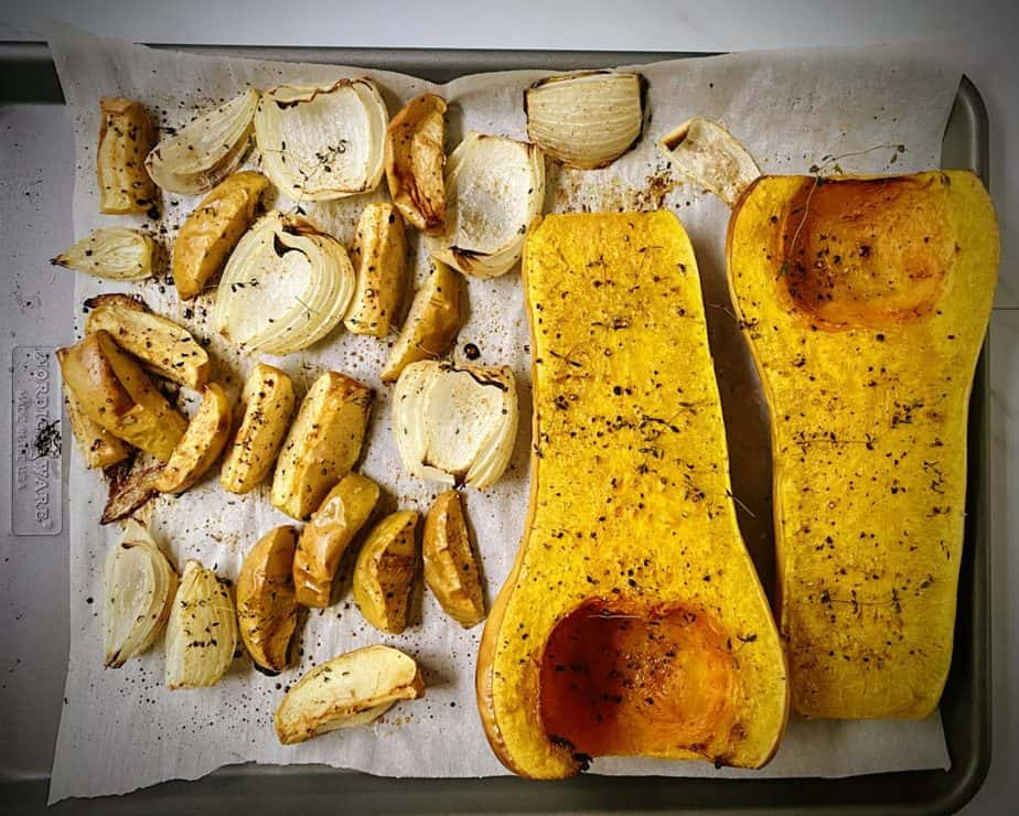 halved butternut squash, apple and onion wedges on a sheet tray after roasting