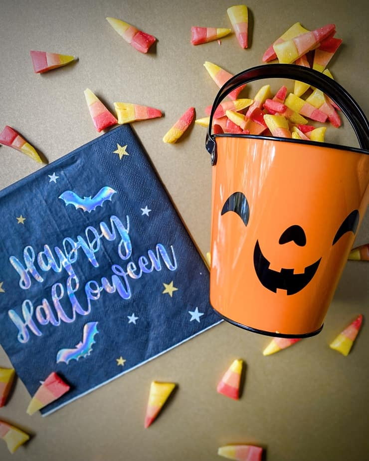 """homemade candy corn with honey spilling out of a bucket that looks like a jackolantern with a black and holographic print napkin that says """"happy halloween"""""""