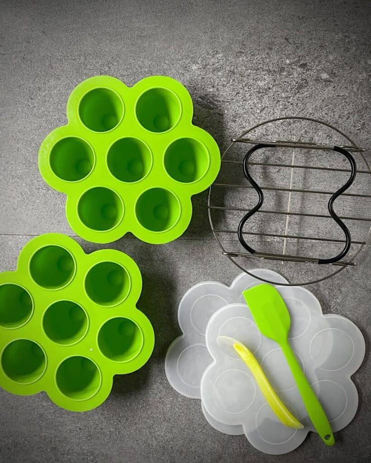 2 neon green egg bite molds with white silicone lids, a lime green mini spatula and scoop-out spoon, and a black Instant Pot trivet with handles