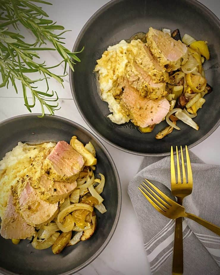overhead shot of two pasta bowls with finished mustard glazed pork with apples, fall veggies, mashed potatoes and pan gravy with fresh sprigs of rosemary, gold forks and a light grey linen on a white marble background