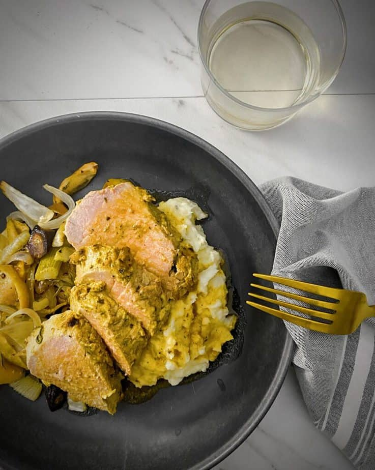 overhead shot of mustard crusted pork tenderloin slices plated on a bed of roasted apples and root vegetables, mashed potatoes and topped with pan gravy in a dark grey pasta bowl with a gold fork, a glass of white wine, and a light grey napkin