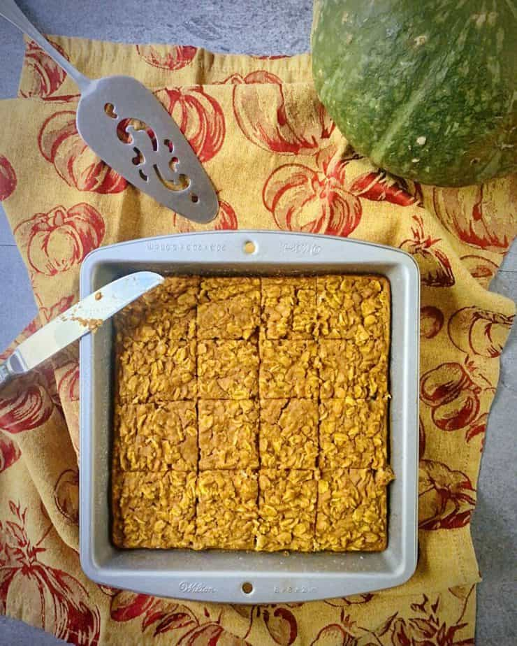 overhead shot of pumpkin baked oatmeal in a square tin cut into 16 squares on a gold and maroon pumpkin themed tea towel