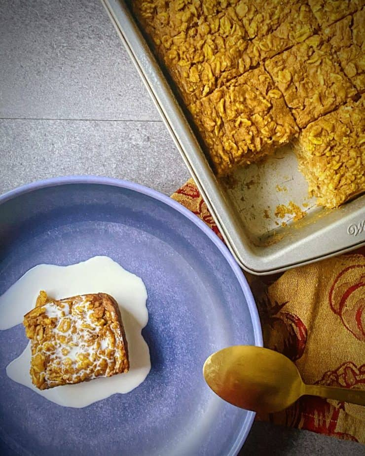 overhead shot of one slice of pumpkin pie baked oats removed from the square tin next to a blue pasta bowl with the slice covered in cream and a gold and maroon pumpkin themed tea towel