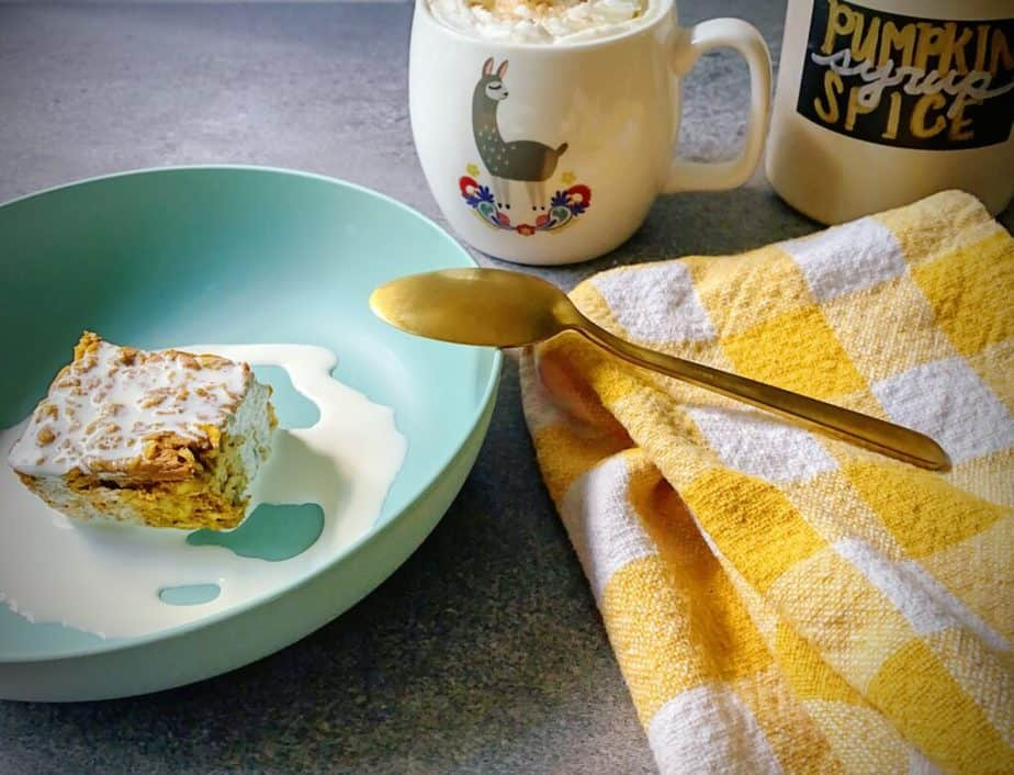 breakfast scene with baked oatmeal topped with cream in a turquoise bowl with a gold spoon, a yellow and white gingham tea towel, a llama patterned mug with a coffee drink topped with whipped cream and cinnamon sugar, and a jug of homemade pumpkin spice syrup