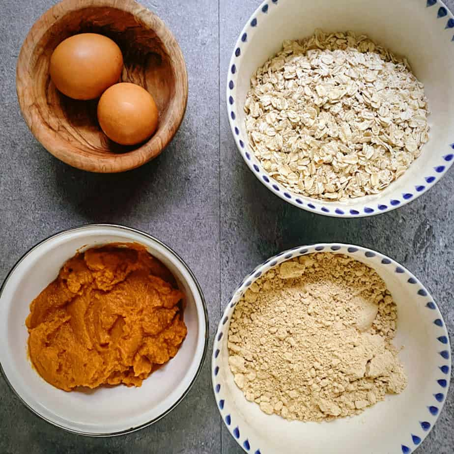 two brown eggs in a wooden bowl, with a blue and white bowl filled with oats, another blue and white bowl filled with peanut powder and a white bowl filled with pumpkin as mis en place