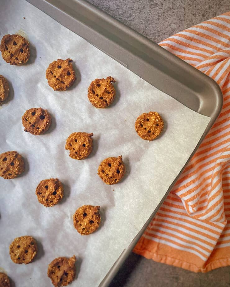 pumpkin peanut dog treats on a parchment lined cookie sheet with an orange and white striped tea towel