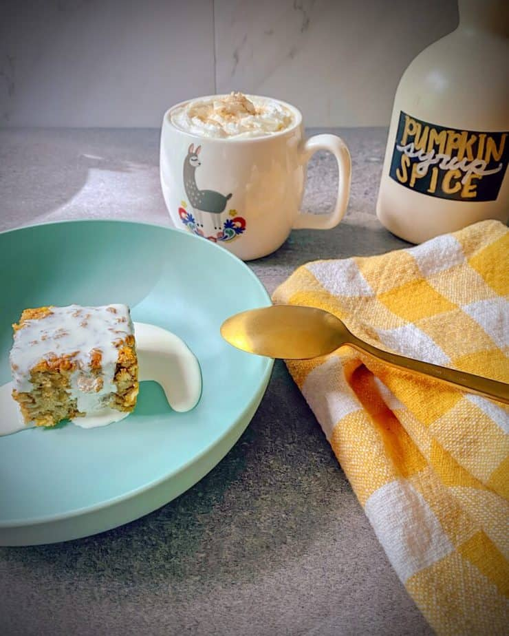 a breakfast spread with a homemade pumpkin spice latte in a llama mug, a jug of homemade pumpkin spice syrup, a slice of my pumpkin baked oatmeal in a turquoise bowl with a yellow and white gingham tea towel