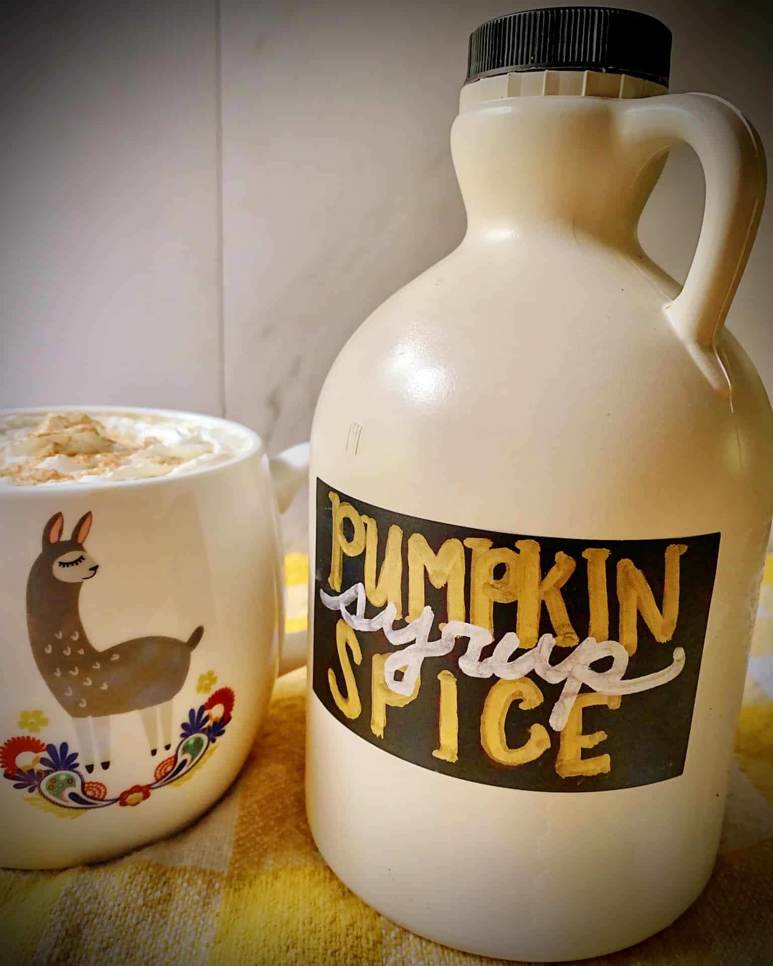pumpkin spice latte with a jug of homemade pumpkin spice syrup