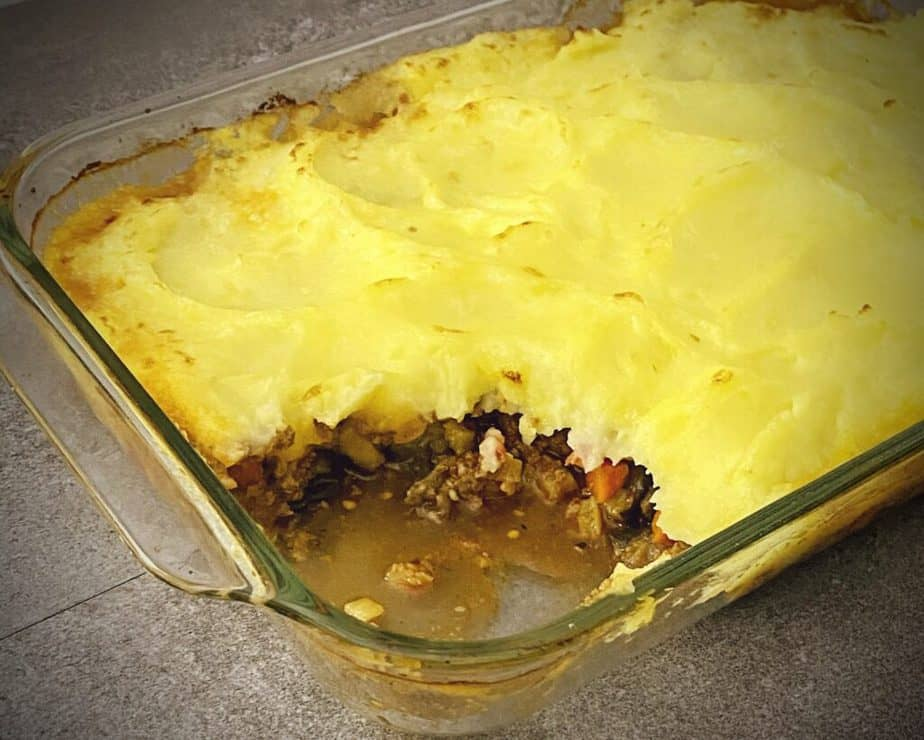 finished moussaka style shepherd's pie in a pyrex 9 x 13 with a scoop out of it