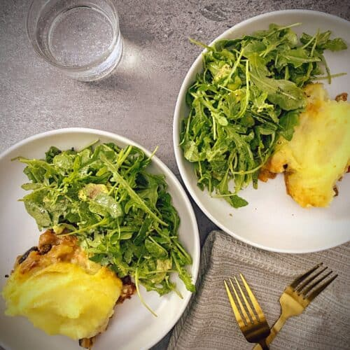 two plates of lamb and eggplant moussaka shepherd's pie with arugula salad in white pasta bowls on a grey slate background with a glass of sparkling water and gold forks