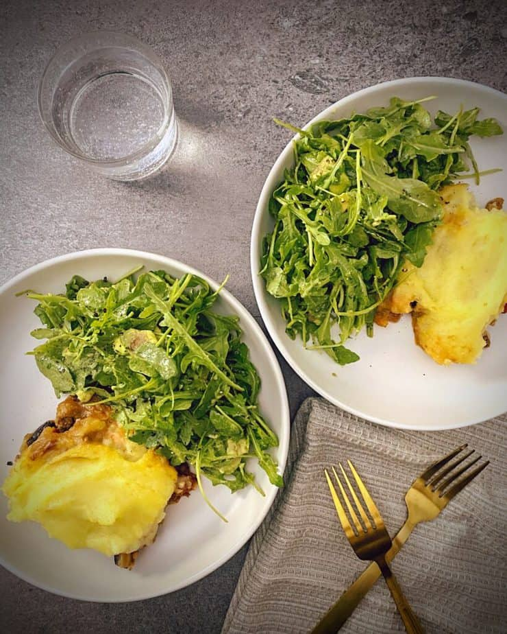 two white pasta bowls with lamb and eggplant shepherd's pie and arugula salad on a grey slate background, gold forks and a tan waffle knit napkin