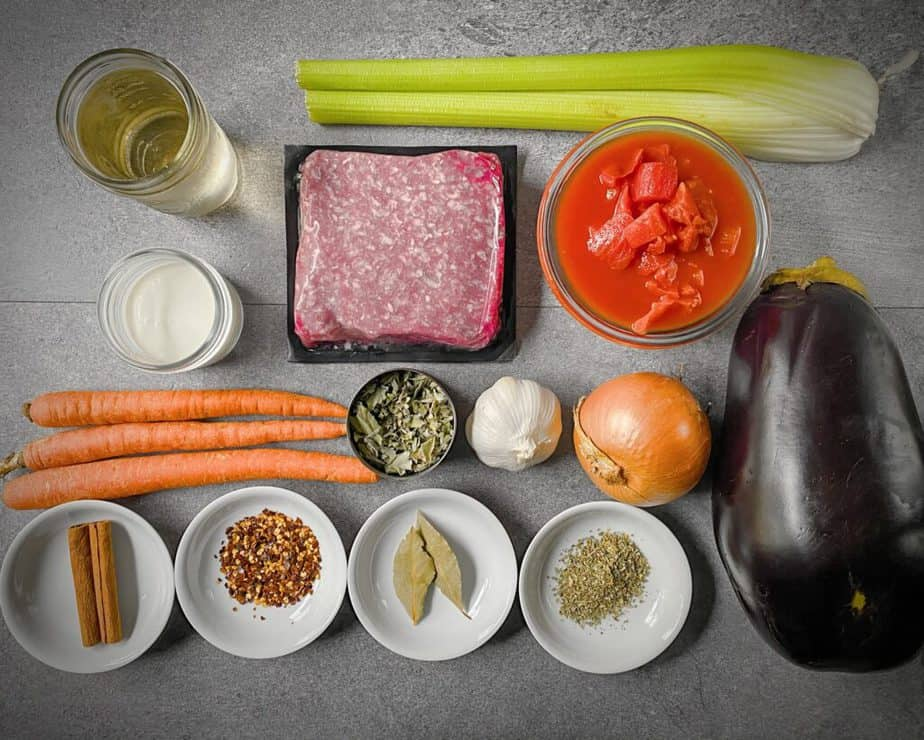 white wine, two ribs of celery, tomatoes in juice, ground lamb, cream, three carrots, dried mint, cinnamon sticks, red pepper flakes, bay leaves, oregano, an eggplant a yellow onion and a head of garlic as mis en place for moussaka shepherd's pie recipe