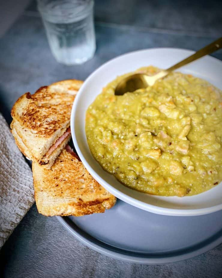45 degree angle shot showing ham and smoked gouda grilled cheese, split pea and ham soup in a white pasta bowl with a gold spoon and a glass of sparkling water in the background on a grey slate table
