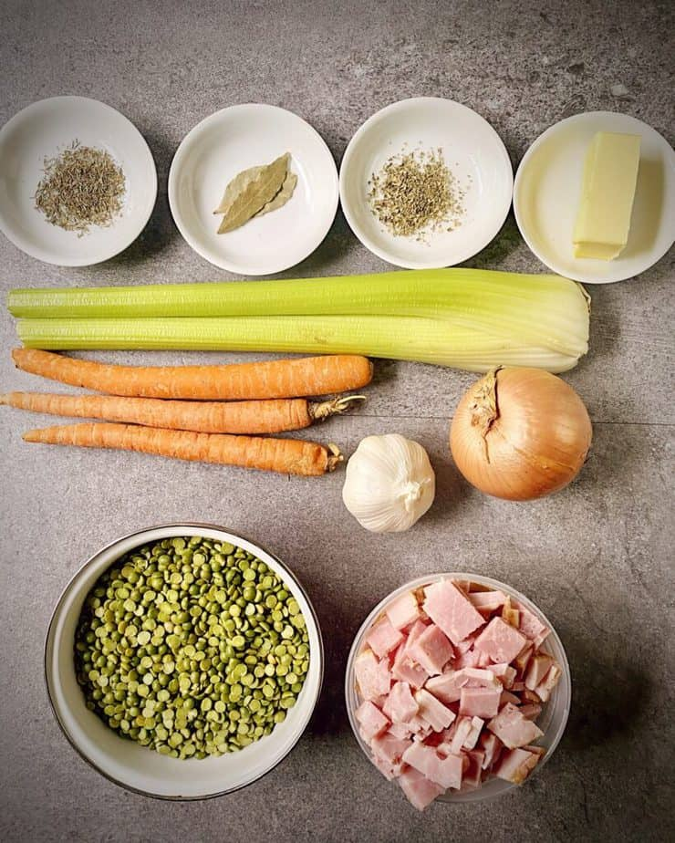 oregano, thyme, bay leaves, butter, 2 celery ribs, 3 carrots, a yellow onion, a head of garlic, chopped ham and split peas as mis en place for split pea and ham soup