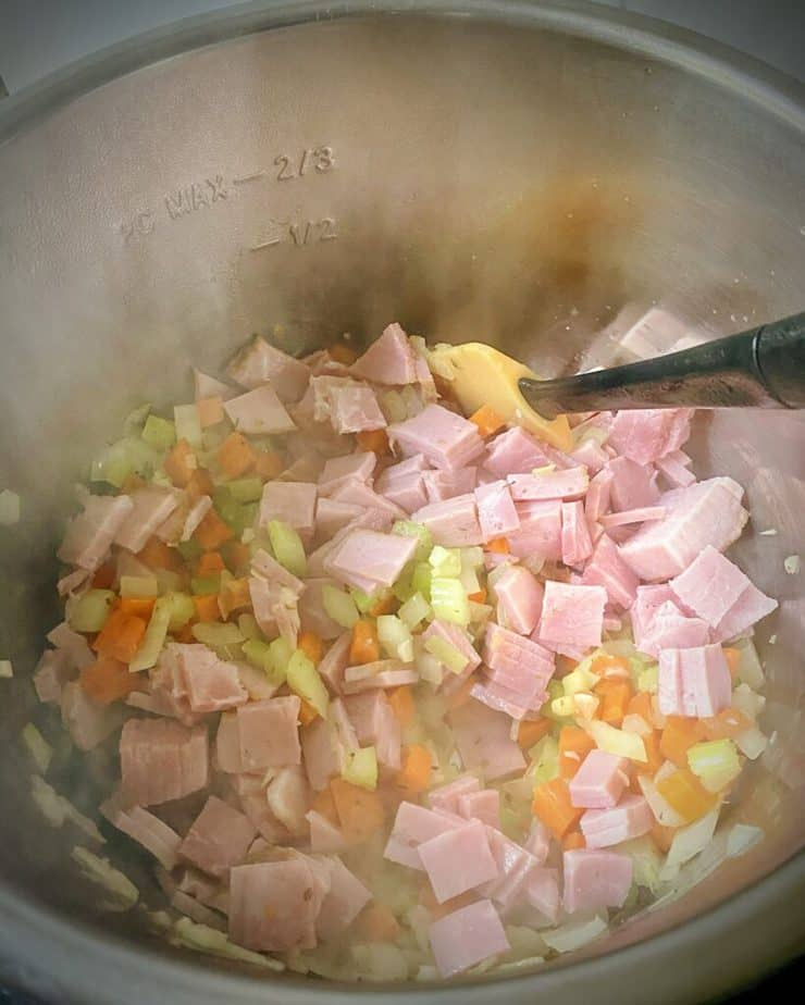 ham and mirepoix cooking in an instant pot for split pea and ham soup