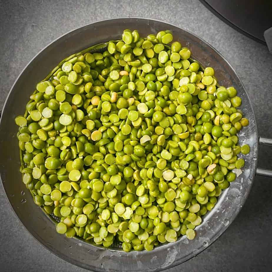 dried split peas in a strainer after being picked through and rinsed