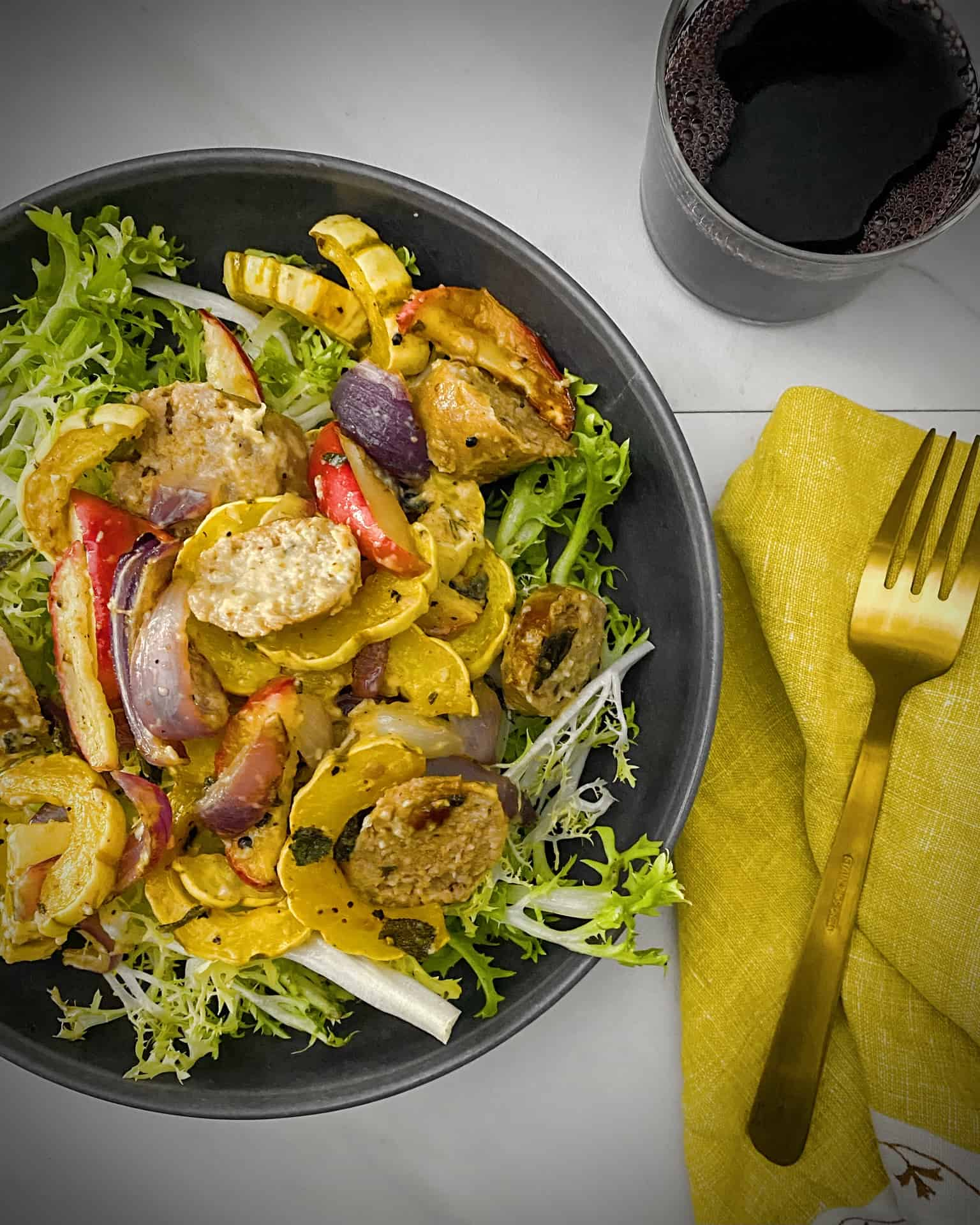 overhead shot of sheet pan pork sausage salad from sun basket in a grey pasta bowl with a saffron yellow napkin, gold fork and glass of red wine