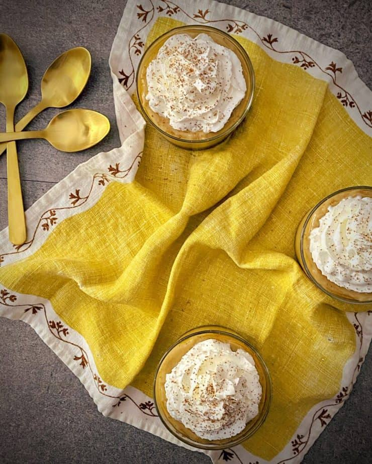 overhead shot of three cups filled with homemade banana pudding and topped with whipped cream and banana shavings on a yellow napkin with white and brown floral border
