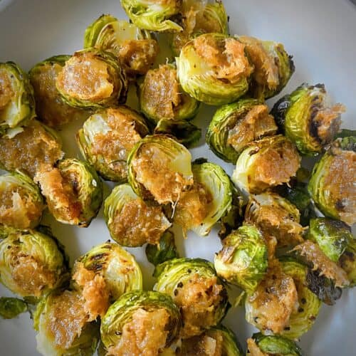 roasted brussels sprouts halves with bacon jam on a grey plate